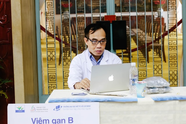 A doctor looking at a laptop screen